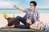 pic of couple sitting beach  - Lovely young couple sitting on mat at beach enjoying holiday and look at something - JPG