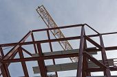 foto of tatas  - A top view of a yellow tower crane and red steel structure on a construction site - JPG