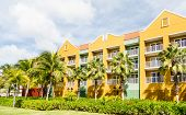 image of curacao  - Brilliant yellow and green plaster resort beyond palm trees in Curacao - JPG