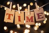 stock photo of time machine  - The word TIME printed on clothespin clipped cards in front of defocused glowing lights - JPG