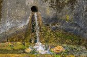 foto of gutter  - Water trickling in a sunny gutter next to a road - JPG