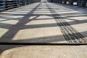 picture of girder  - Cast Iron girders throw shadows onto a walkway for pedestrians - JPG