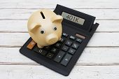 picture of calculator  - Saving for your retirement A golden piggy bank on a calculator with word 401k over a distressed wood background - JPG