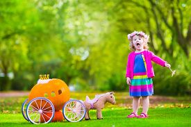 image of fairies  - Cute curly little girl playing Cinderella fairy tale holding magic wand next to a pumpkin carriage in autumn park at Halloween - JPG