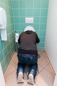 foto of vomiting  - Man kneeling and vomiting in the toilet - JPG