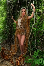 pic of jungle animal  - Attractive young woman in luxury animal print dress among the jungle - JPG