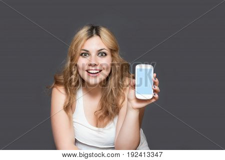 Laughing attractive long haired teenage girl is showing smart phone with blank touchscreen looking at the camera. All is on the gray background. All potential trademarks and buttons are removed.