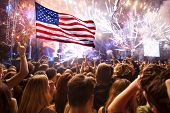 Crowd of people celebrating Independence Day. United States of America USA flag with fireworks backg poster