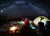 Night Camping Near The Town. Young Couple Enjoying Near Campfire And Tent, Looking At Beautiful Nigh poster