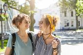 Two Student Female Companions Standing At Campus During Break Gossiping About Boys. Women In Sunglas poster