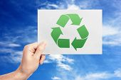 Concept of environmental conservation and protection. Man holding paper with symbol of recycling on  poster