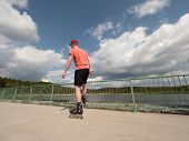Постер, плакат: Roller Skater In Action Man Ride In Inline Skates Ride Along Promenade Handrail Sky In Background