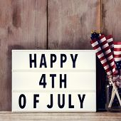 a lightbox with the text happy 4th of july and some american flags on a glass jar, on a rustic woode poster