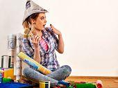 Repair home woman holding paint brush for wallpaper. Female in newspaper cap renovation apartment. P poster
