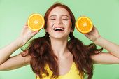Image of a beautiful excited young redhead girl posing isolated over green wall background with citr poster