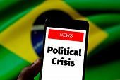 Holding Cell Phone With The News On The Screen political Crisis. Brazil Flag On Blurred Background poster