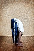 stock photo of surya  - Indian man in white shirt doing second step of surya namaskar uttanasana forward bending pose indoors on wooden floor at grunge background - JPG