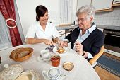 stock photo of geriatric  - a geriatric nurse helps elderly woman at breakfast - JPG