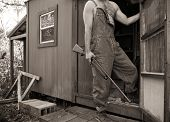 stock photo of redneck  - Sepia photo of shirtless man in overalls holding a shotgun guarding his backwoods camp or shack - JPG