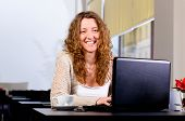 stock photo of casual woman  - young woman is sitting at cafe and working on laptop - JPG