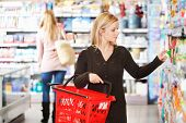 stock photo of grocery-shopping  - Young woman carrying basket while shopping in the supermarket - JPG