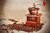 stock photo of wooden box from coffee mill  - Contrast image of vintage coffee mill or grinder with coffee beans  - JPG