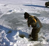 image of ice fishing  - a small boy ice fishing in alberta