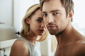 A close up portrait of two young people in love posing in the kitchen. Love affair, interior. poster