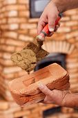 Постер, плакат: Строительство каменной кладки нагреватель крупным планом на руках работника