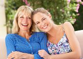 stock photo of grown up  - Senior Woman With Adult Daughter Relaxing On Sofa At Home - JPG
