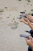 stock photo of shooting-range  - Closeup of hands aiming guns at firing range - JPG