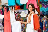 stock photo of hippy  - Woman shopping summer colorful dresses and clothes in street market - JPG