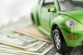 stock photo of speeding car  - Toy car and money over white  Rent - JPG