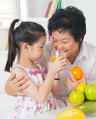 Asian family drinking orange juice. Happy Asian grandchild sharing cup of fresh squeeze fruit juice