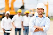 stock photo of hispanic  - Male architect at a construction site looking happy - JPG