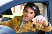 stock photo of car key  - young man sitting inside car showing keys to car - JPG