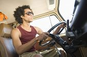 stock photo of campervan  - Low angle view of a young man driving campervan - JPG