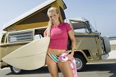 stock photo of campervan  - Portrait of a smiling young woman holding surfboard against campervan - JPG