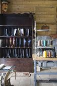 Footwear on shelves by sewing machine at traditional shoemaker workshop