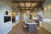 pic of stool  - View of stools at island with chandelier and wood beamed ceiling in kitchen - JPG