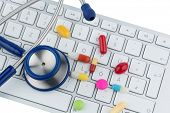 tablets on keyboard symbol photo for online pharmacies and drug costs