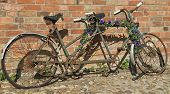 stock photo of tandem bicycle  - Rusty abandoned tandem bicycle against brick wall - JPG
