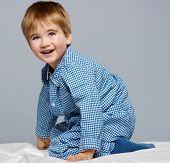 image of pyjama  - Little boy wearing blue pyjamas in bed - JPG