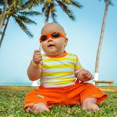 picture of laughable  - Cute baby sitting on a grass - JPG
