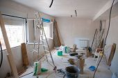House indoor improvements in a messy room construction with plaster tools and ladder