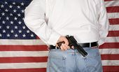 A under cover police officer or concerned citizen has a .45 caliber Pistol Concealed in his back wai