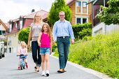 Young family with Mother, father and daughters walking through a housing estate, perhaps they make a