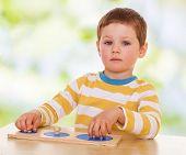 picture of montessori school  - little boy engaged in Montessori kindergarten - JPG