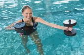 stock photo of day care center  - Fit blonde working out with foam dumbbells in swimming pool at the leisure centre - JPG