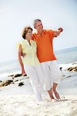 picture of old couple  - Happy mature couple walking along the beach - JPG